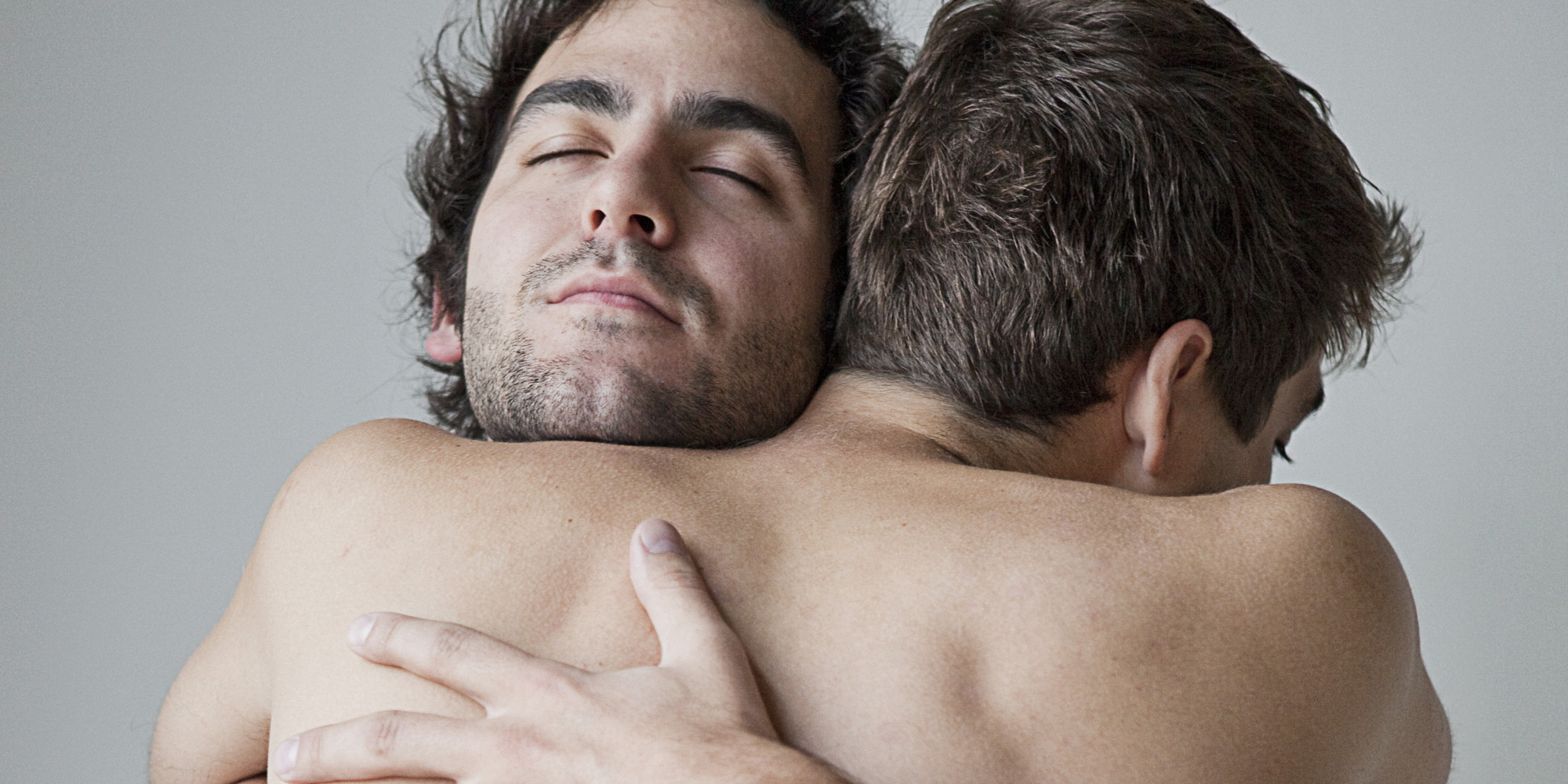 Gay Couple Embracing In The Couch By Wavebreakmedia
