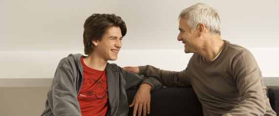 Mature man with his son sitting on a couch and gossiping