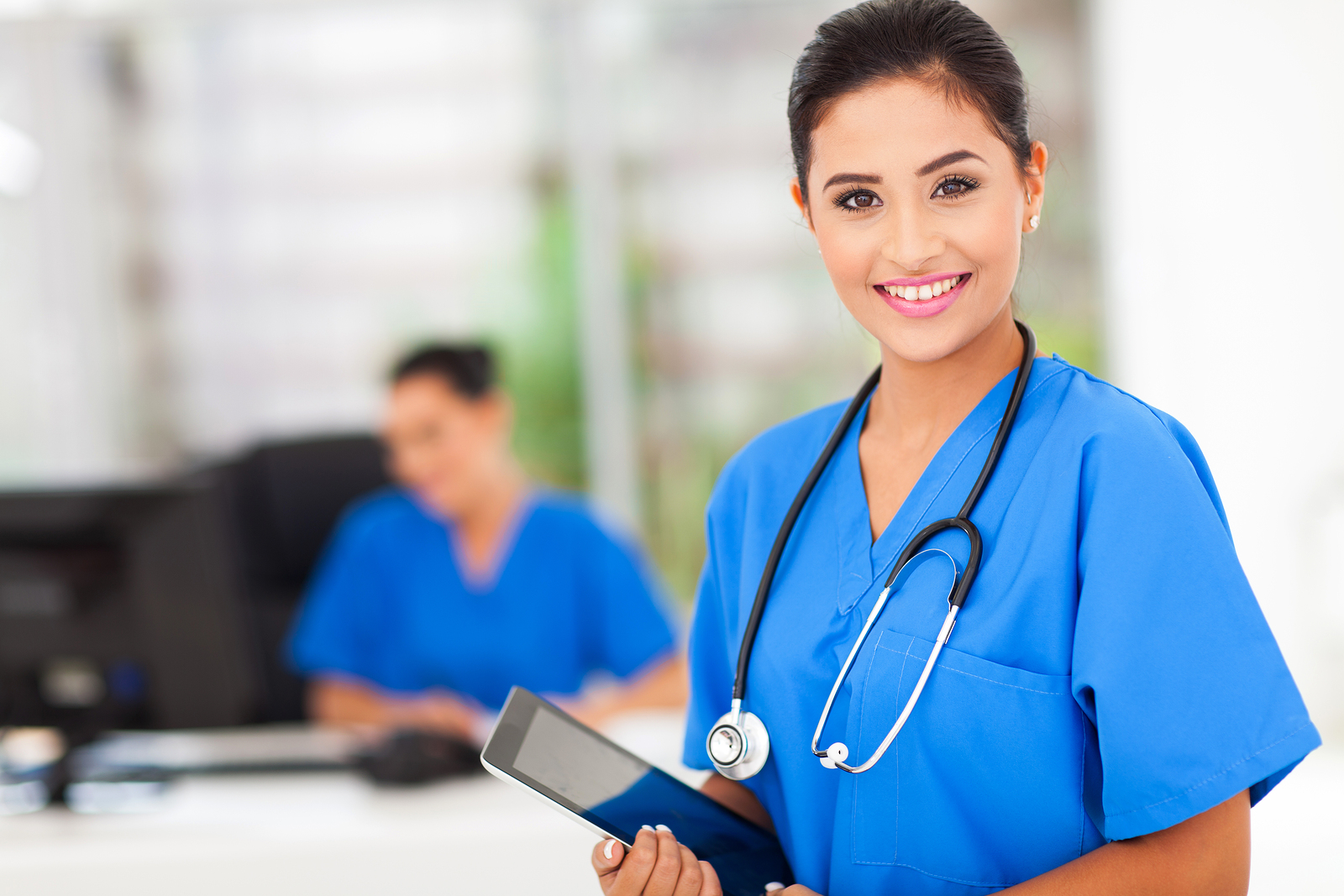 attractive young female nurse holding tablet computer at workpla