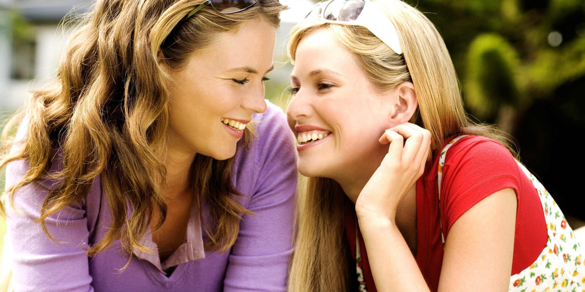2 young smiling women lying on grass, looking at each other
