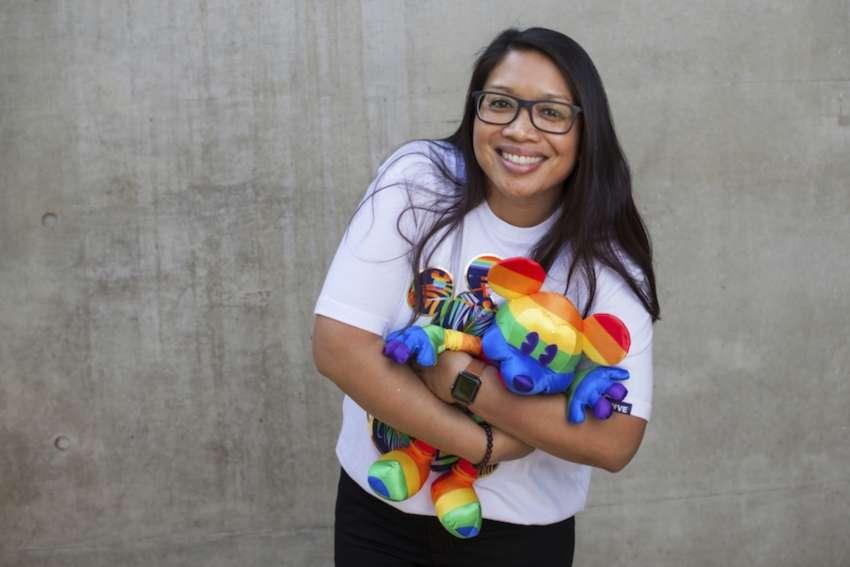 a girl with long dark hair holds a rainbow mickey mouse