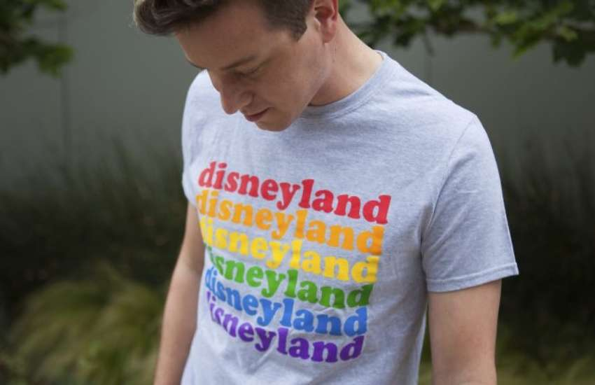 a man in a grey t-shirt he is looking down at and it has the word disneyland written over again in rainbow colours