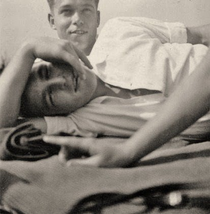 A vintage photo of a young gay couple cuddling.