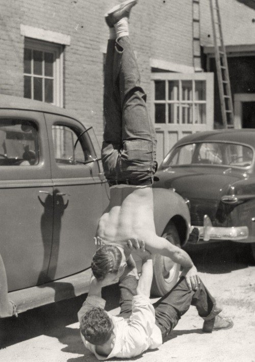 A photo of a gay couple doing handstands.
