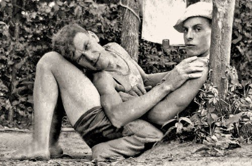 A vintage photo of a gay couple cuddling.