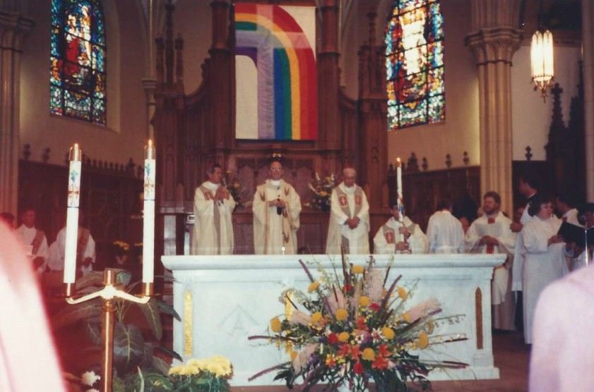 a groups of priests stand at the pulpit, behind them is a giant rainbow flag with a clear cross over the top of it